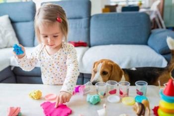 Собака и ребенок играют с пластилином